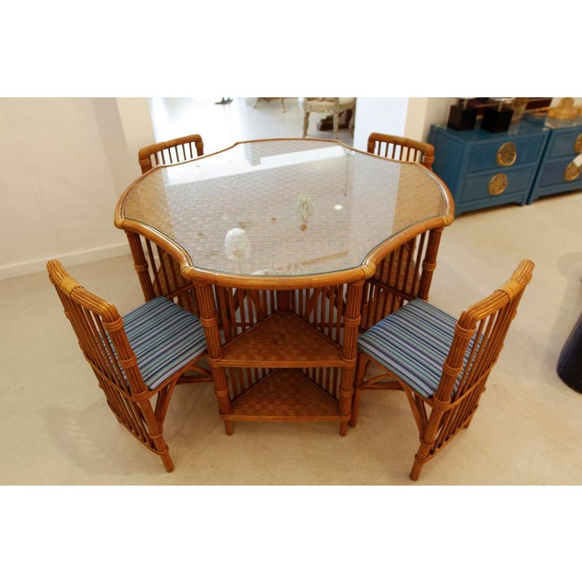 Vintage rattan set of table and four chairs which tuck underneath to make it very compact -- ideal for small spaces.