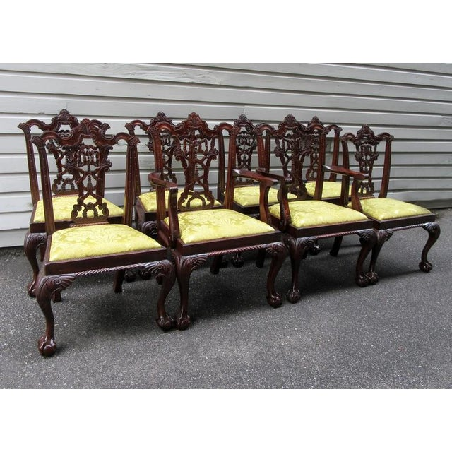 A set of eight English Chinese Chippendale mahogany dining chairs, circa 1900, featuring finely carved ribbon and tassel...