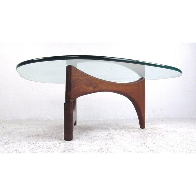 """Solid walnut base with heavy 3/4"""" glass top, this classic midcentury table is in the style of Isamu Noguchi for Herman..."""