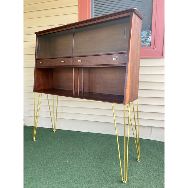 This brilliant Display Cabinet is made of wood, solid wood, walnut wood, walnut veneer, and glass with long gold metal...