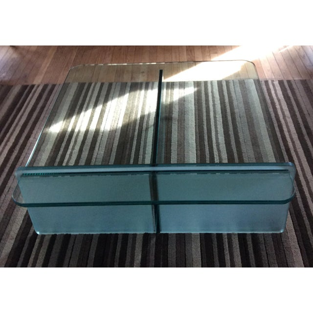 "Striking all-glass coffee table made of three intersecting 3/4"" panes of glass. One pane is frosted. All have a blue-green..."