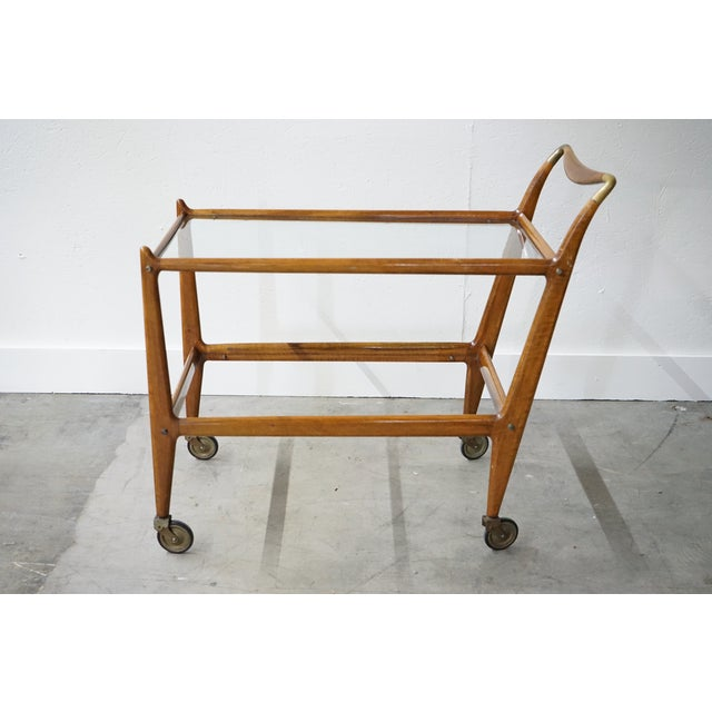 This is an elegant vintage teak framed bar cart with glass top and shelf from France, circa 1940s featuring brass accents...