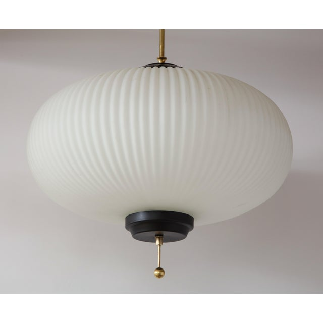 Stilnovo ribbed milk glass globe lantern/chandelier with lacquered black hardware and brass canopy and columnar support. A...