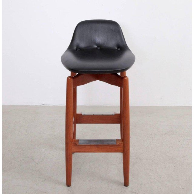 Pair of teak barstools with upholstered black leather seats and a low back.