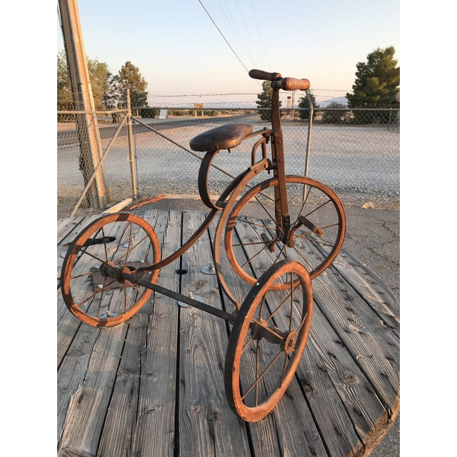 This is a well loved antique child's tricycle made from metal, cast iron, wood and leather. The body of the trike is...