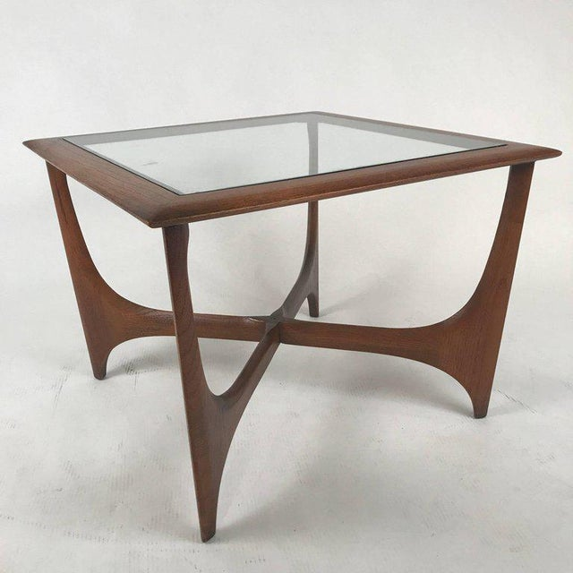 Sculptural end table from 1967 constructed of walnut and glass. Gorgeous classic midcentury design.