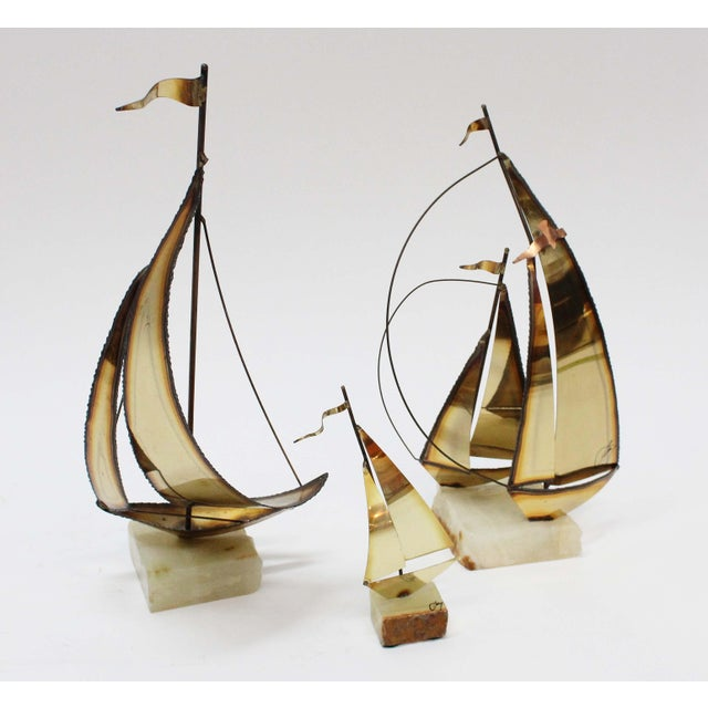 "Set of 3 Brass Boats on a stone base. Each three vary in size. Boats are signed by the artist. Large: W: 7"" D: 3"" H:..."