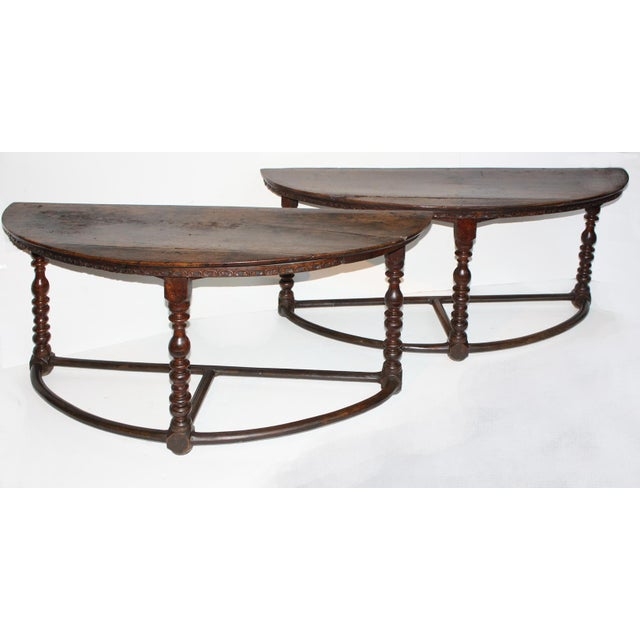 A pair of large demi-lune consoles made of walnut with turned legs and T-stretchers with a carved apron, old repairs to...