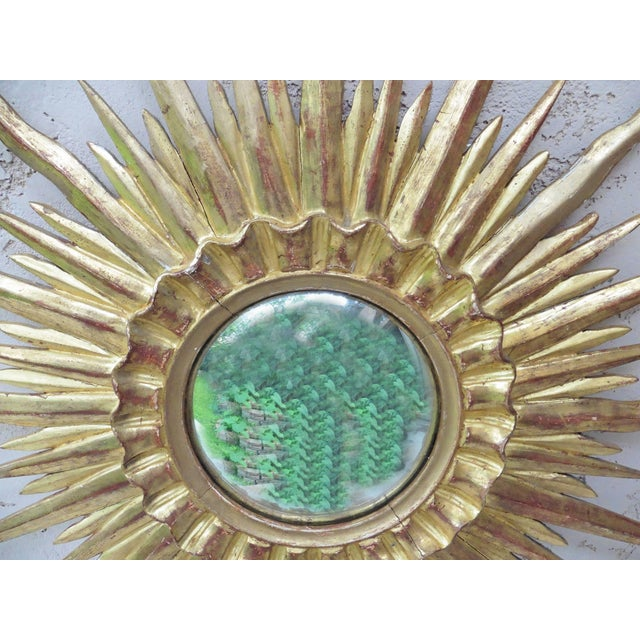 Large stunning French convex sunburst gilded wood mirror, circa 1950. A gorgeous wall accent!