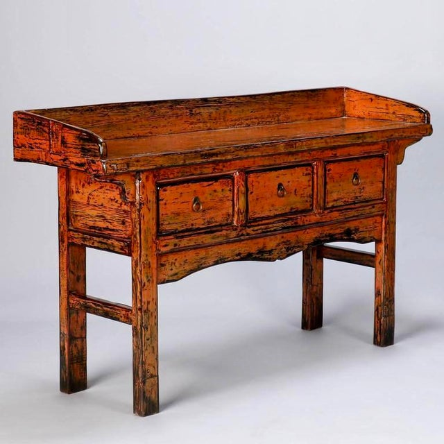 Early 20th century Chinese painted three drawer console table in dark orange painted and lacquered finish with brass...