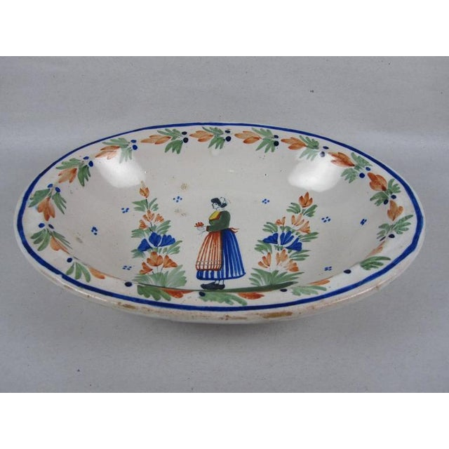 From the Grand Maison Quimper, an oval open vegetable server in the Couronnes pattern, circa 1920's. A floral garland with...