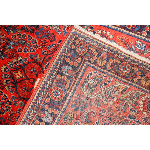 Antique handmade Persian Sarouk rug in red colour. The rug is in original good condition from the beginning of 20th century.