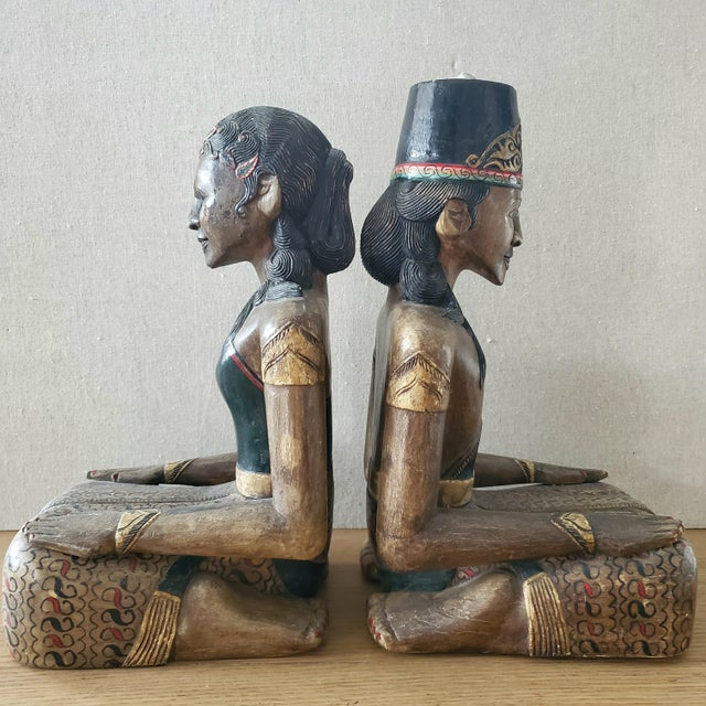 A pair of Indonesian hand carved and hand painted wood kneeling statues; male & female. While uncertain the exact source,...