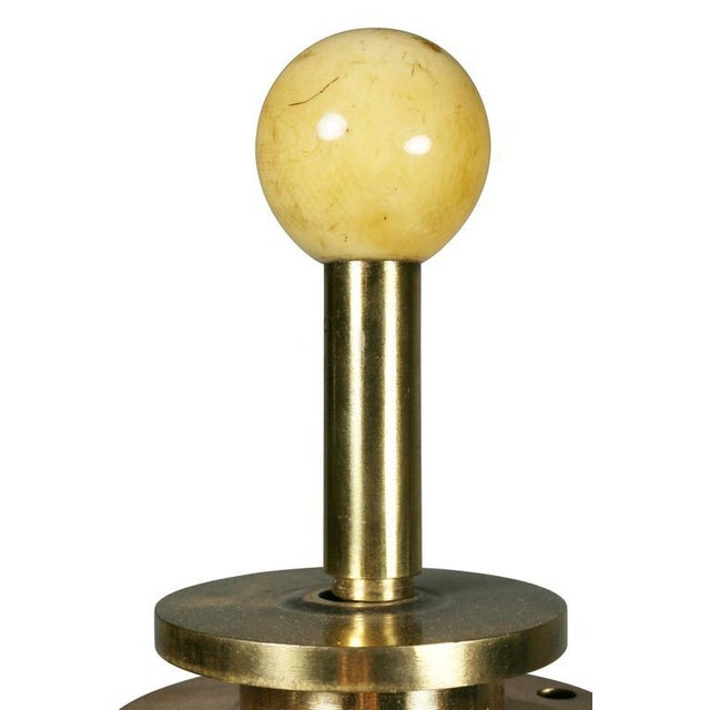 With ball finial over two lights and two pull chains cylindrical support and weighted stepped circular base.