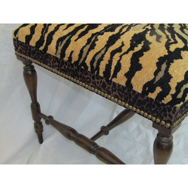 Versatile upholstered bench. Featuring Tiger print fabric, brass tack edging and turned wood legs. This fresh bench can...