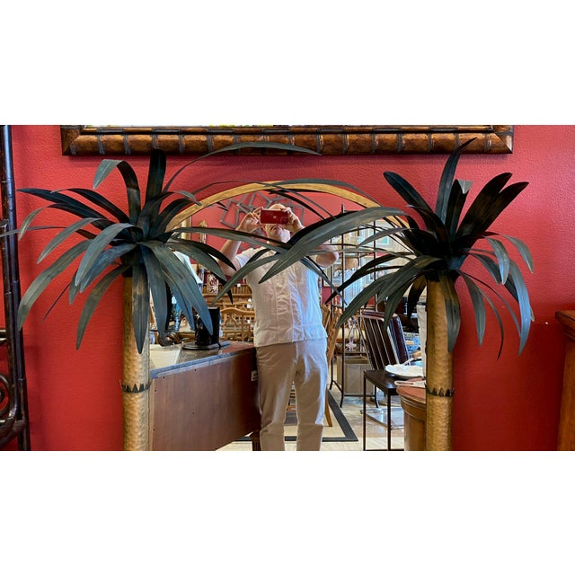 Wall mirror framed between between 2 painted metal palm trees. This Palm Beach Regency mirror is a perfect bit of whimsy...