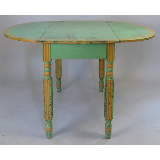 A very charming antique 1920s drop leaf dining table, in its original hand painted finish in light fern green with orange...