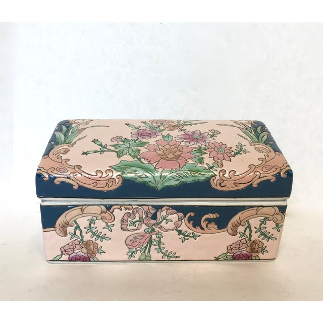 Chinese hand-painted porcelain lidded box finished with pale pink color glaze with pink lotus blossom and navy accents. No...
