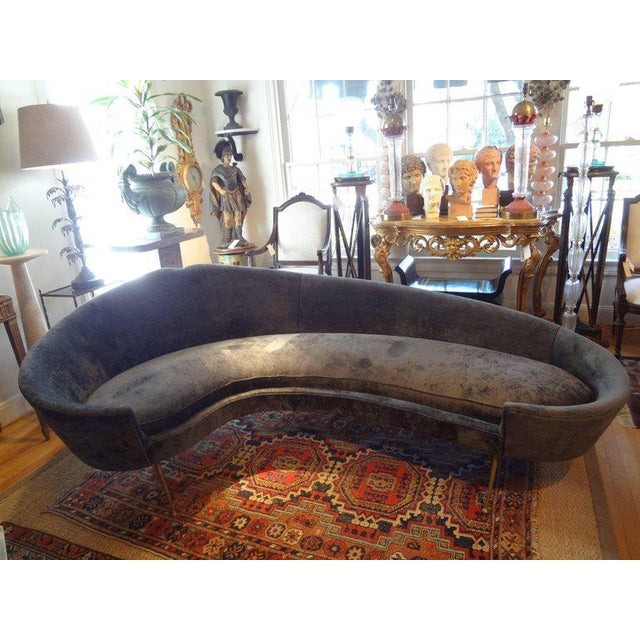 Gorgeous Italian midcentury curved sofa with splayed brass legs attributed to Federico Munari, circa 1960. In the style of...