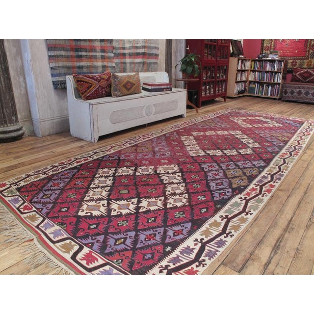 A large tribal Kilim from Southern Turkey, woven in two symmetrical halves, as is typical of nomadic work, featuring a...