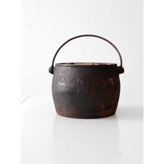 This is an antique cast iron pot with bail handle. The black iron pot features a worn enamel lined interior. It has a...