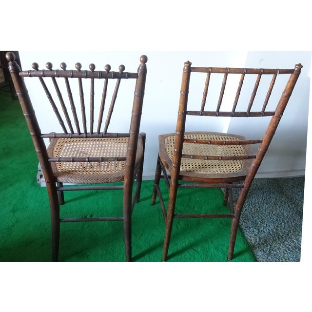 "Antique twin faux bamboo chairs. They are not identical. Each has a cane seat, one with a small ""dent""."