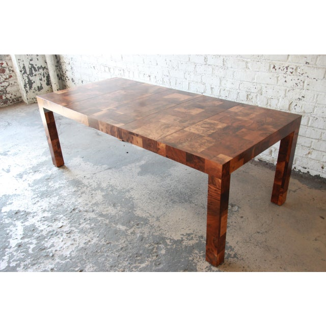 Offering a rare and exceptional mid-century modern Parsons style patchwork burl wood dining table designed by Paul Evans...
