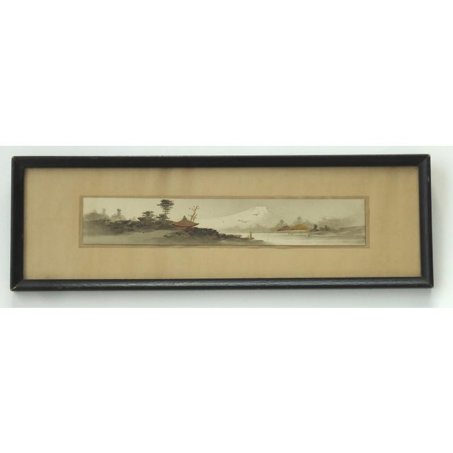 An antique Japanese landscape painting in black ink, gold, red and white paint. In a simple black frame, antique label on...