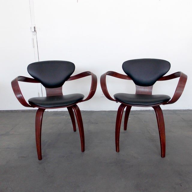 Attributed to Norman Cherner, this pair of pretzel arm chairs is made from molded plywood, with black leather seats and...