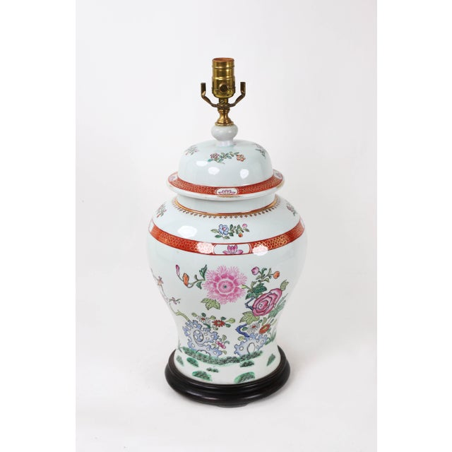 Famille Rose temple jar lamp with decorative depictions of indigo colored rocks, flower blooms, buds, berries, and grass.