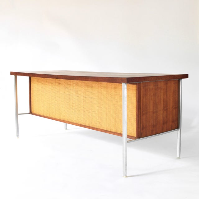 About this Cane and Walnut Executive Desk by Costa Mesa in the style of Florence Knoll. Presenting this exceptionally rare...