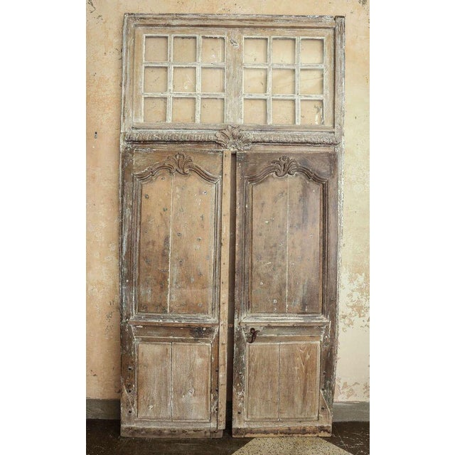 Large-scale transomed Louis XV doors: Régence period exterior doors, hand-carved in oak with original transom. Dated to...