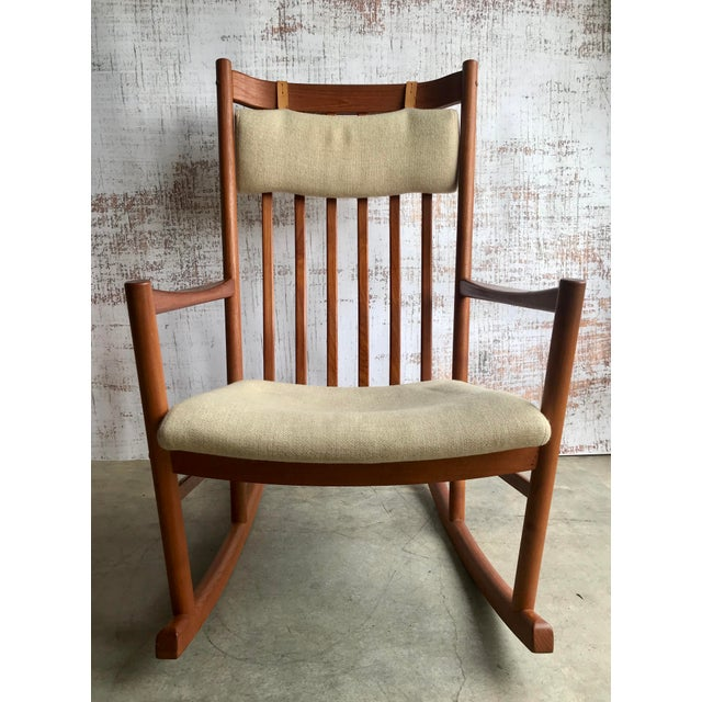 Teak rocking chair designed by Hans Wegner for Tarm Stole made in Denmark. Chair features original off white wool...