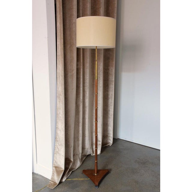 A 20th century French elegant floor lamp by Maison Lunel in its beautiful original condition designed in a solid wooden...