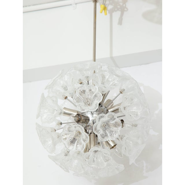 Elegant Italian floral Sputnik chandelier. The chrome armature supports clear and opaque floral glass elements with light...