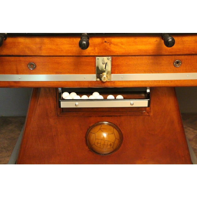 This foosball table is very unusual because it has got light honey color wood and the players are silver polished...
