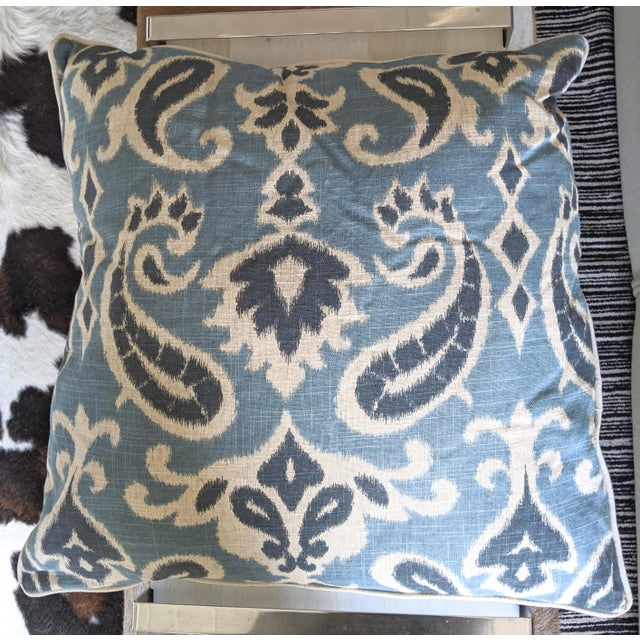 A pair of striking, ikat pillows in a linen-blend fabric featuring variegated shades of muted blues, with edged piping and...