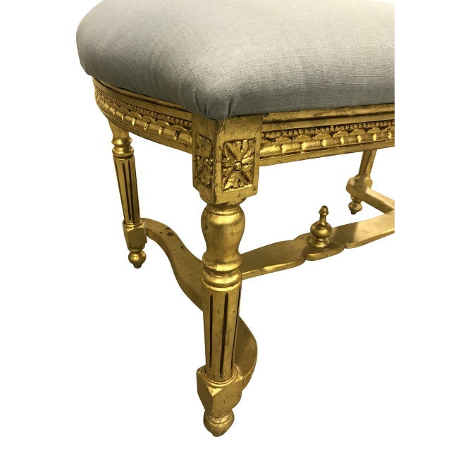 Vintage Louis XVI style French gilded boudoir bench. Recently reupholstered in a light blue linen.