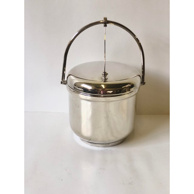 Late 20th Century sleek and polished silverplate ice bucket with an attached easy open swing top and a white interior...