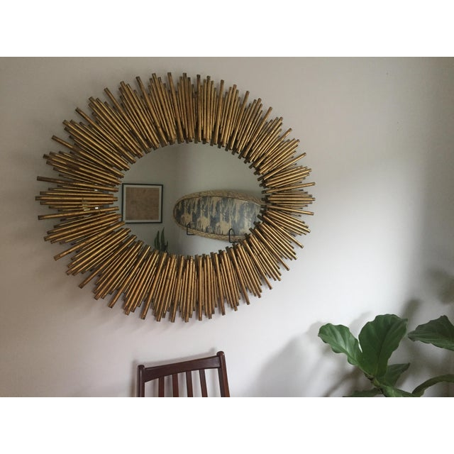 Large-scale oval wall mirror features a sunburst pattern by Arteriors Home with a rim of thin textured iron reeds in...