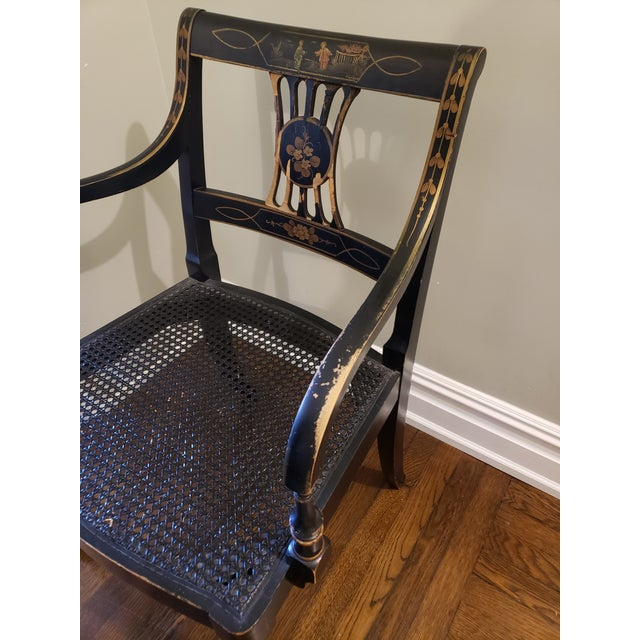Pair of vintage Regency style occasional armchairs with cane seats. Decorated with gilded ornamentation, antiqued black...