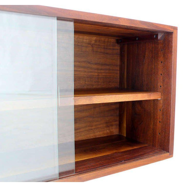 Very nice mid century modern hanging shelf with sliding glass doors.