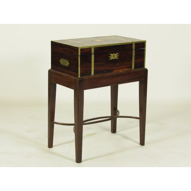 An early 19th century English Regency rosewood campaign lap desk on later custom mahogany stand with brass binding...