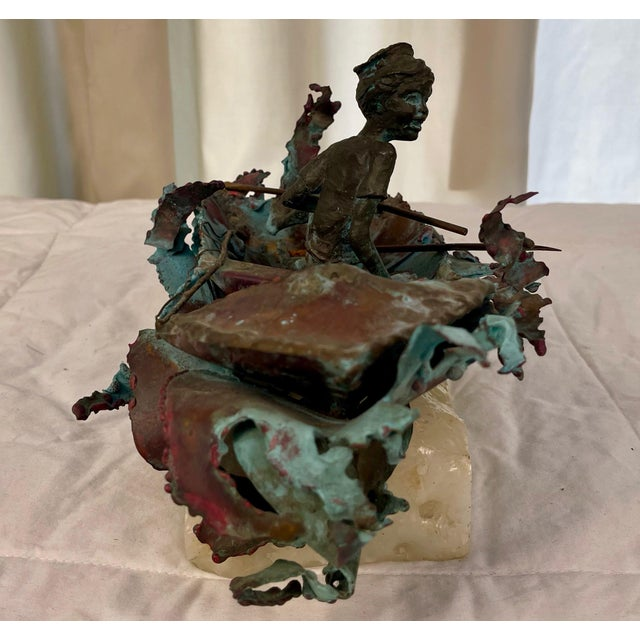Whimsical sculpture of boy fishing in small boat. Exquisite detail with waves, fishing pole, fish in boat and faux bronze...
