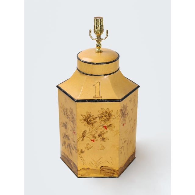 The metal hexagonal tea caddy lamp is painted yellow with brown flowers painted on it. The number 1 represents tea leaves...