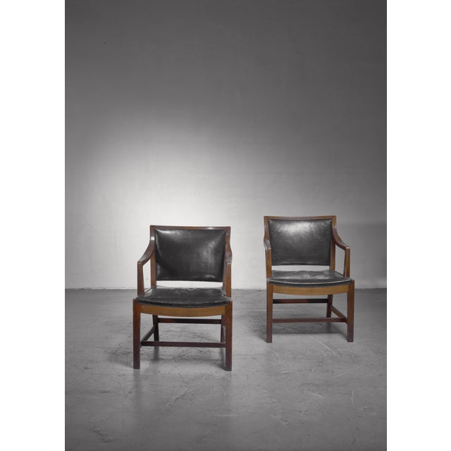 A rare pair of armchairs made of stained beech, upholstered with a dark green leather. These chairs were designed for and...