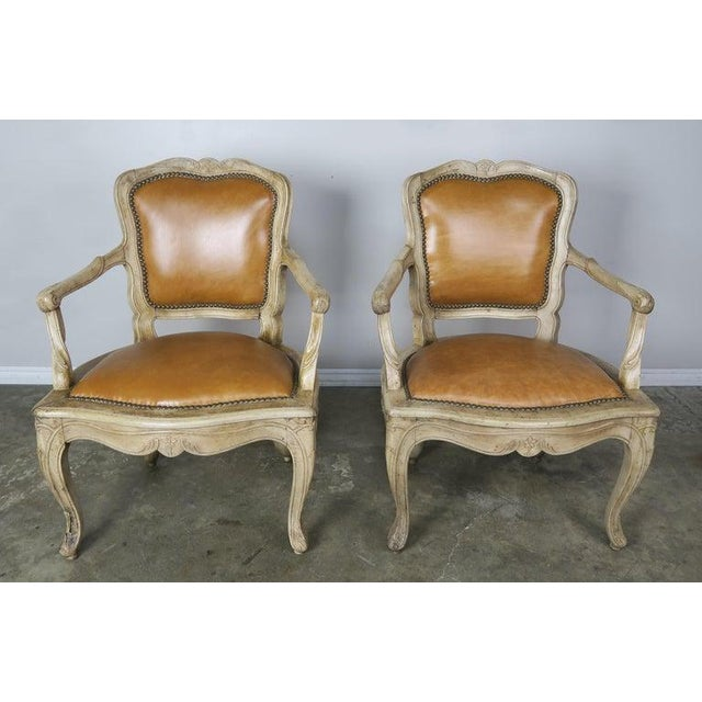 Pair of French walnut Louis XV style carved bleached walnut armchairs upholstered in a caramel colored leather with brass...