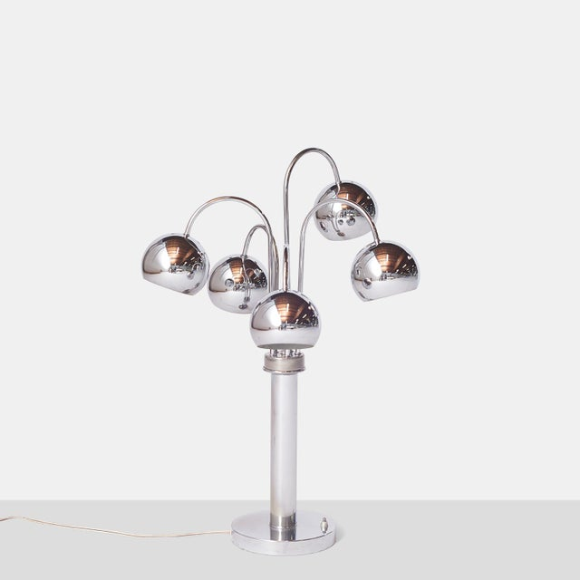 A table lamp in chrome with five arms and round shades. Each arm swivels to adjust the light direction. Off/on switch...