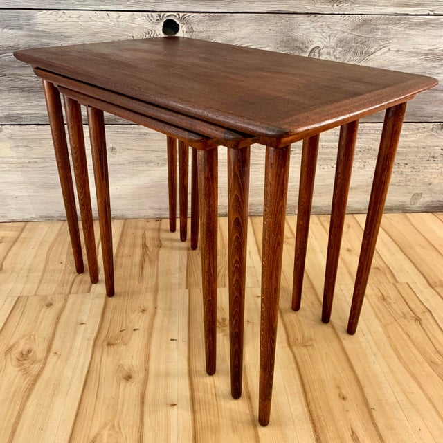Set of three Danish Modern teak nesting tables. Tables slide into grooves, locking them together. Price is for the set....
