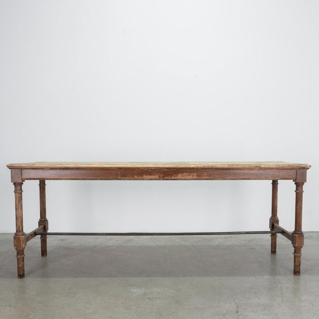 A wooden table with iron trestle bar, from Belgium, circa 1900. Ornamental carved legs are dressed with a textured brown...